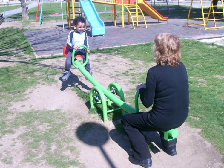 My son, on top of the seesaw, happy, playing with his grandma.
